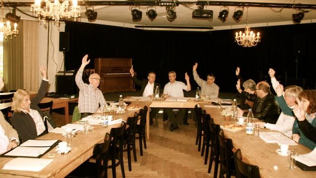 Ein Saal mit Tischen und Personen, die eine Abstimmung durchführen.