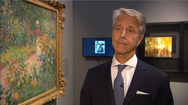 Mann steht neben einem Bild in Museum
