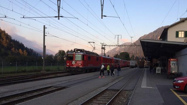 In tren charrescha en la staziun da Glion ils passagiers spetgan sin ils tren.