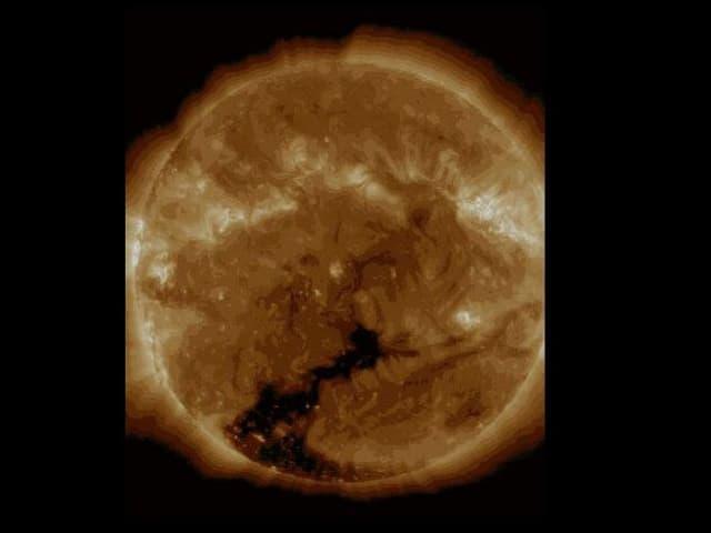 Gelb-orange Sonnenscheibe mit Gashülle darum herum. Alles scheint in Bewegung. Unten ist ein grosses, dunkles Loch zu sehen.