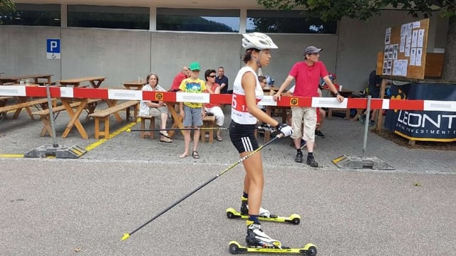 Eine Nachwuchs-Athletin auf Roll-Ski mit Stöcken