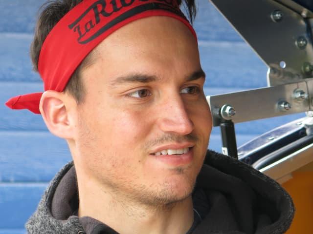 Der Kopf von Zbinden, er trägt ein rotes Stirnband mit Aufschrift.
