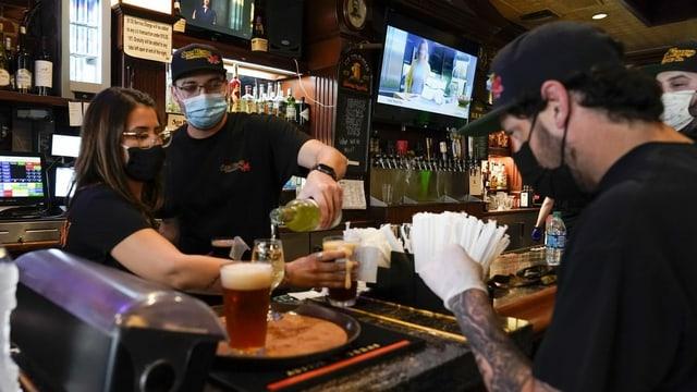Personen mit Masken bereiten an einern Bar Drinks vor.