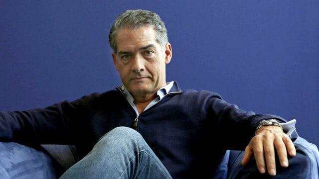 Kerr sitzt vor einer blauen Wand auf einem Sessel