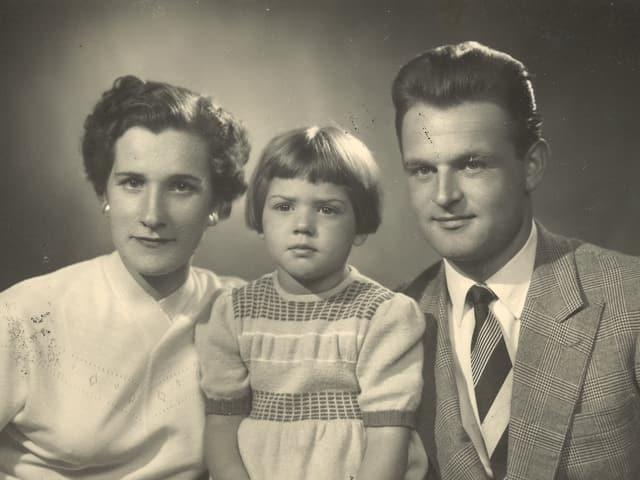 Alte Fotografie mit einem Elternpaar und ihrer kleinen Tochter in der Mitte.