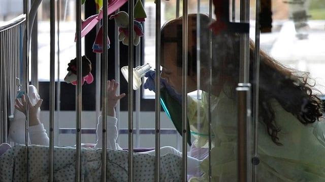 Kind streckt in einem Spitalbett die Arme hoch, eine Frau hält eine Beatmungsmaske.