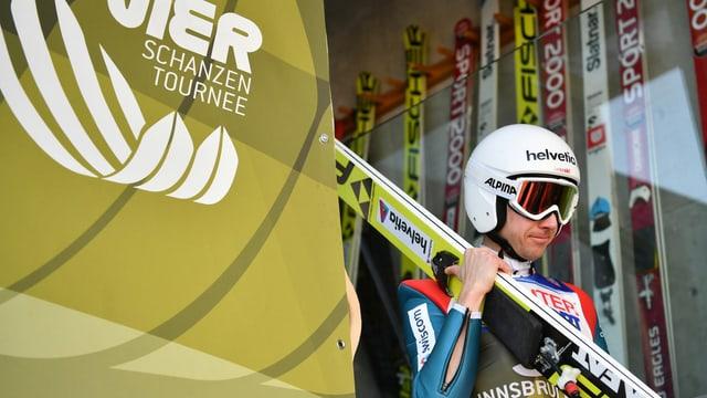 Simon Ammann trägt seine Skis.