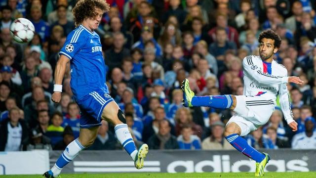 Zu sehen ist der FC Basel Spieler Mohamed Salah, der einen Ball um David Luiz von Chelsea zirkelt. Salah trägt das weisse Auswärtstrikot des FCB, Luiz spielt ganz in blau. Im Hintergrund sind die Zuschauer eines Champions League Spiels zu erkennen.
