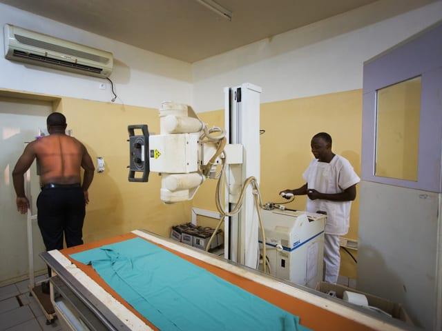 Ein Patient wird geröntgt, während ein Mann inw eisser Kleidung ungeschützt daneben steht.