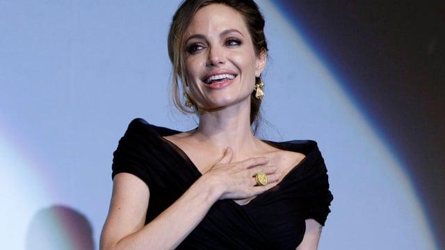Angelina Jolie in einer Abendrobe hält sich die Hand auf die Brust und lächelt.