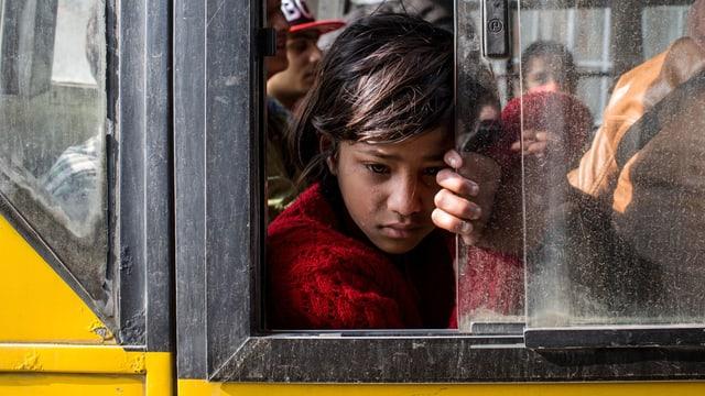 Ein trauriges, nepaleisches Mädchen schaut aus dem Fenster eines Autobusses.