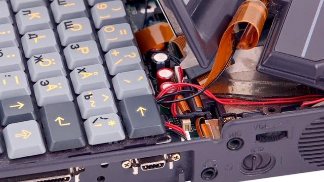 Aus einem geöffneten Laptop hägen verschiedene Kabel.