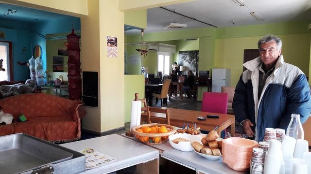 Ein Mann steht in einer improvisierten Kantine. Vor ihm liegt ein Frühstücksbuffet.