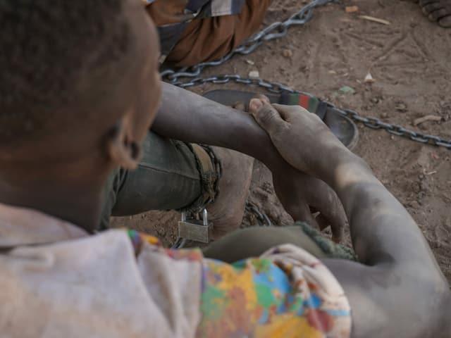 Mann sitzt im Staub, am Bein eine Kette