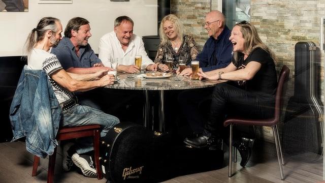 Sechs Bandmitglieder sitzen an einem Tisch und trinken ein Bier.