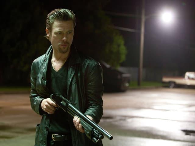Schauspieler Brad Pitt mit einer Pump Gun in der Hand.