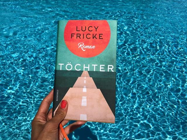 Annette König hält das Buch von Lucy Fricke: «Töchter» vor blaues Wasser