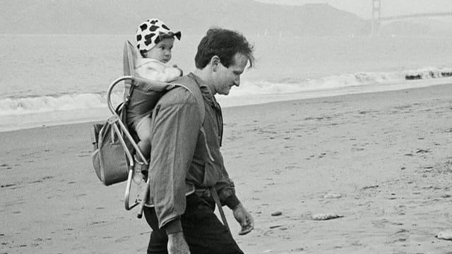 Williams mit Kleinkind auf Rücken am Strand