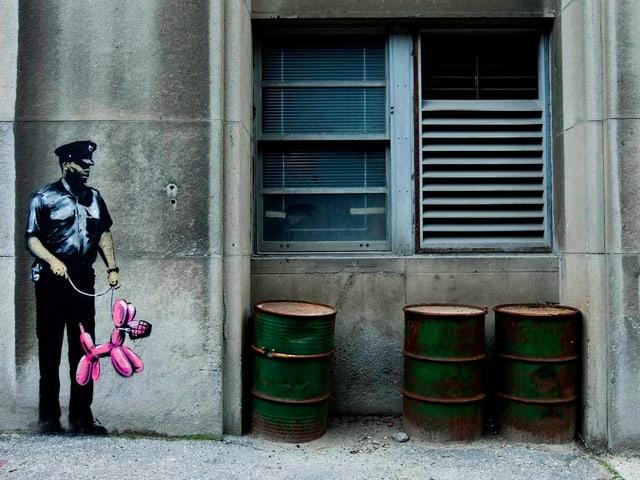 Auf einer grauen Wand ist ein Polizist aufgemalt, der einen pinkfarbenen Ballonhund an der Leine hält.