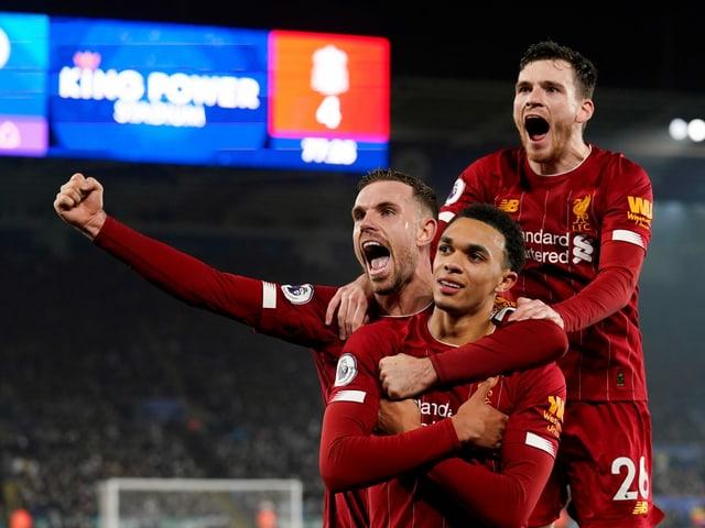 3 Liverpool-Spieler jubeln gemeinsam, indem sie in die Höhe springen.