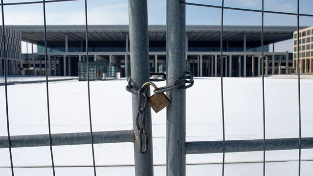 Umzäunung mit einem Vorhängeschloss vor dem Flughafen Berlin Brandenburg (BER).