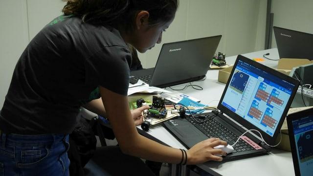 Ein Mädchen beugt sich über einen Laptop.