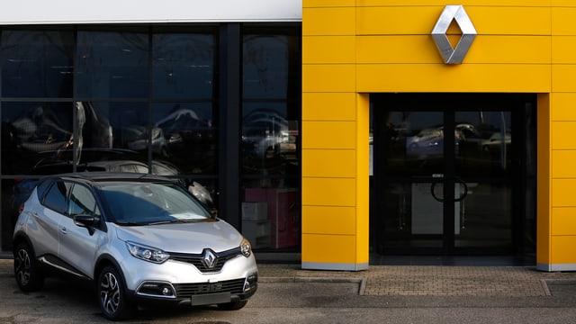 Renault-Auto vor einer Verkaufsstelle, rechts die Eingangstür in gelb mit dem Firmenlogo darüber