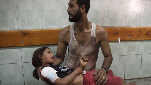 Ein Mann hält ein verletztes Mädchen.