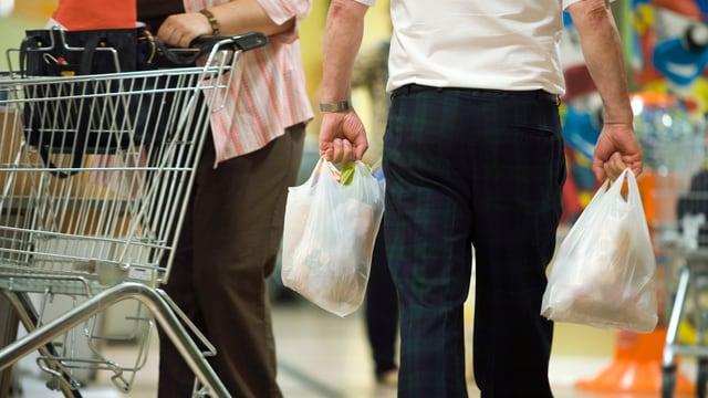 Eine Person trägt zwei Plastiksäcke.
