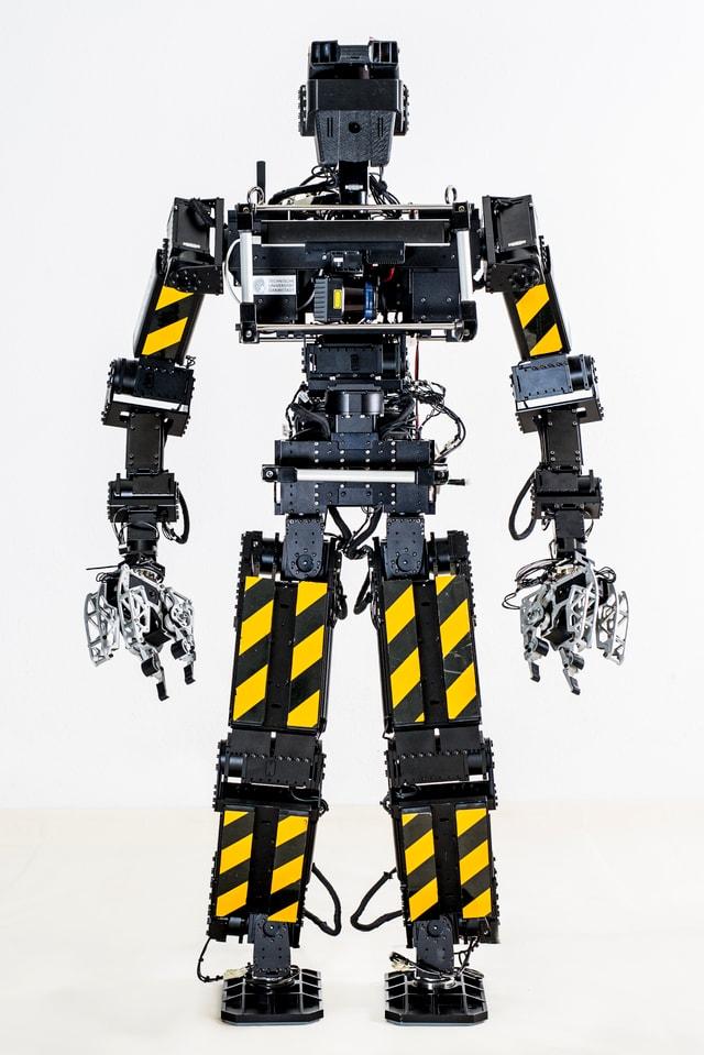 Ein menschenähnlicher Roboter mit Armen und Beinen, auf denen gelbe Streifen angebracht sind.