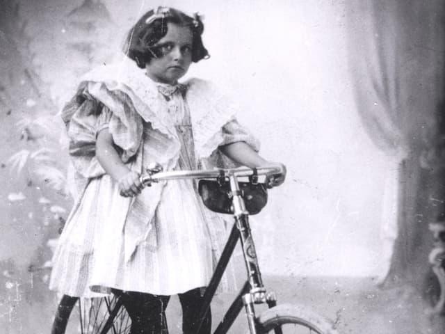 Schwarz-Weiss-Fotografie von einem kleinen Mädchen auf einem Fahrrad.