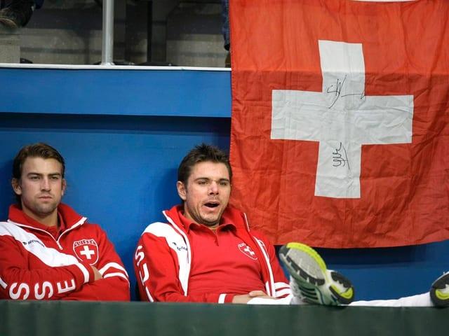 Michael Lammer und Stan Wawrinka sitzen frustriert im Stadion. Wawrinka gähnt. Im Hintergrund hängt eine Schweizer Fahne.