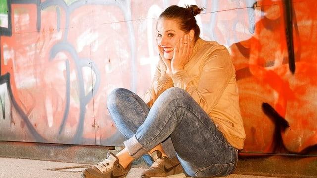 Frau in Jeans und Jacke sitzt am Boden und hält sich das Gesicht.