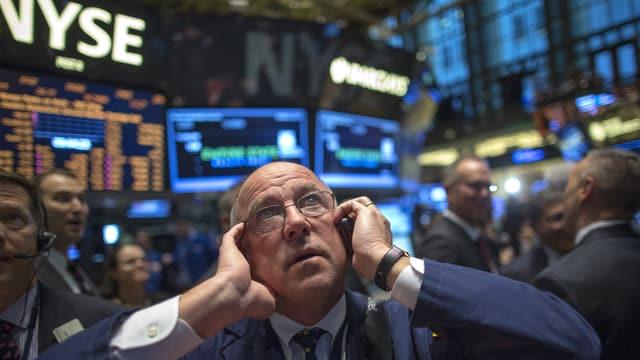 Ein Börsenmakler telefoniert und hält sich ein Ohr zu.