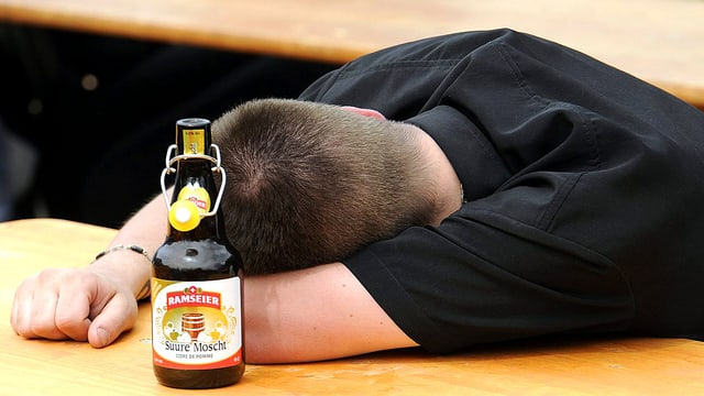 Betrunkener schläft auf einem Festtisch. Neben ihm steht eine Flasche saurer Most.