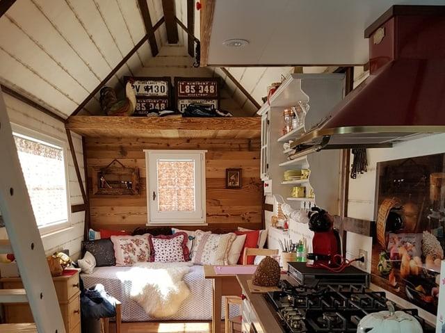 Ein kleines Haus mit einem Sofa mit vielen Kissen darauf.