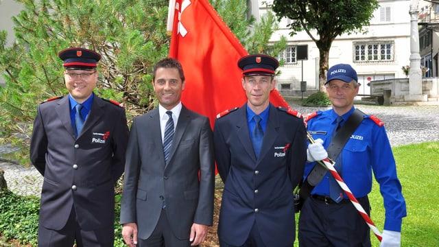 Vier Männer, drei davon in Polizeiuniform, vor einer Schwyzer Fahne.