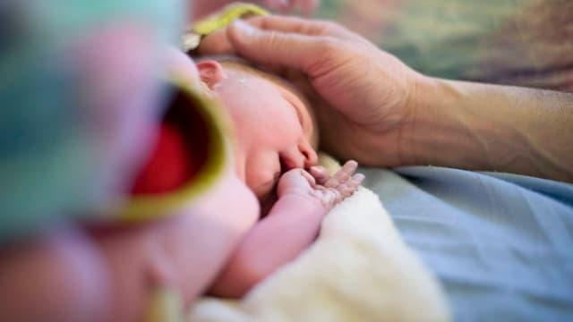 Neugeborenes liegt nackt auf Tüchern und eine erwachsene Person streicht ihm über den Kopf.