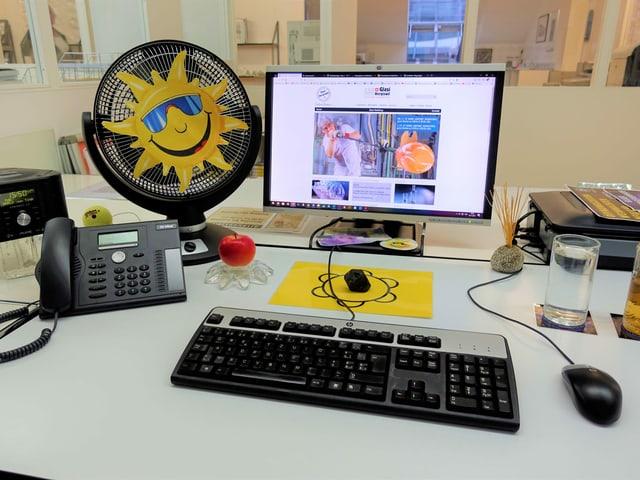 Schreibtisch mit Computer, und Ventilator mit ausgeschnittener Sonne drauf
