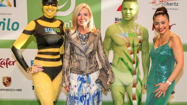 Silvia Matthäus an einem Event zwischen Menschen, die mit Körperfarbe bemalt sind.