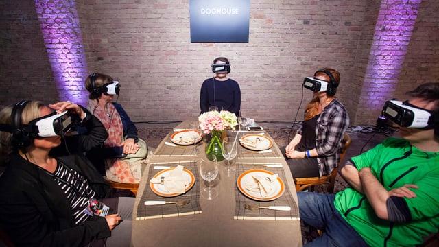 Menschen sitzen an einer gedeckten Tafel. Sie haben alle auf VR-Brille auf.