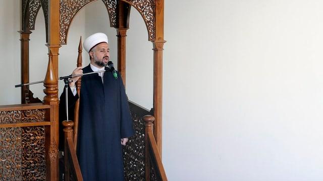 Der Imam unter einem hölzernen Baldachin.