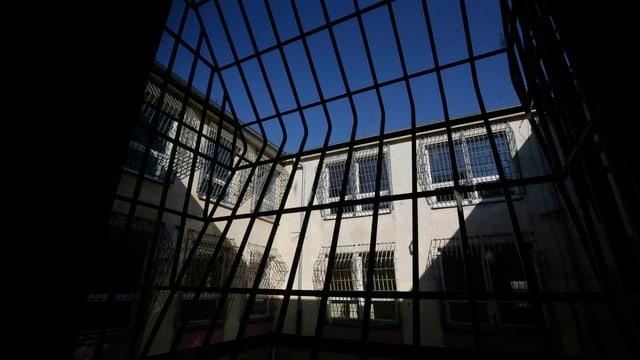 Blick in einen vergitterten Gefängnis-Innenhof, weit oben ein Stückchen blauer Himmel.