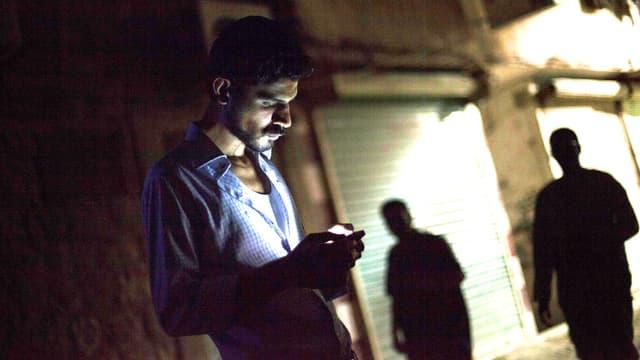 Ein Mann schaut auf sein Handy.