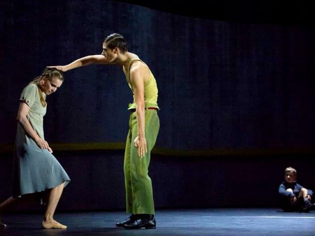 Mann drückt Frau mit Hand auf den Kopf, im Hintergrund sitzt ein Junge am Boden.