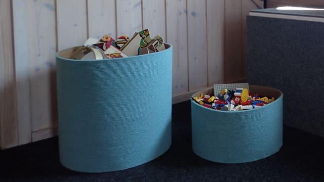 Türkisfarbene Aufbewahrungsbehälter aus Teppich und Holz.