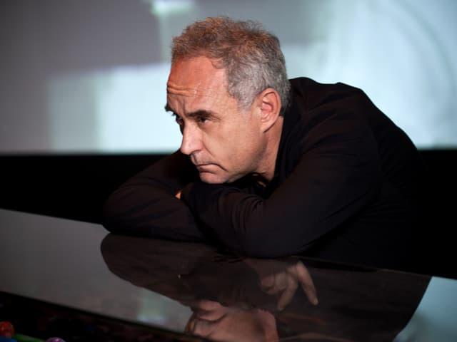 Ferran Adriá, auf einen glänzenden Tresen gelehnt, nachdenklich zur Seite blickend.