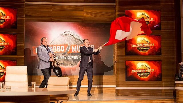 Viktor schwingt eine Schweizerfahne, Mike schwingt eine Kuhglocke.