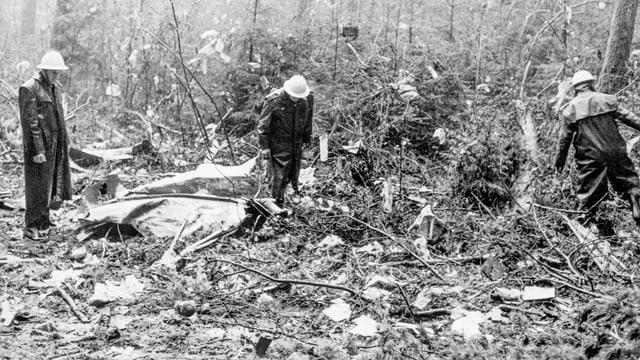 Schwarzweissfotografie. Polizisten im Wald. Trümmerteile am Boden.