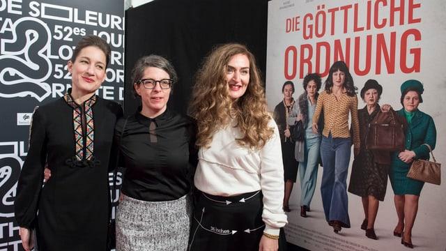 Drei Frauen vor Filmplakat